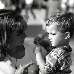 "Black and white photo: Mom and young son outside. Son is in mom's arms, signing ""hurt"" with a sad look on his face. Mom's free hand is mirroring sign ""hurt""."