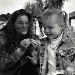 "Black and white photo: Mom and daughter outside at a park. The daughter is in motion, blond hair in short pigtails, pushing a toy, her right hand in a ""three"" handshape. Mom is looking at her signing ""more"". Both are smiling gently."