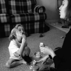 "Black and white photo: Mother and daughter in a living room, sitting on the carpet with a mini tea set between them. Young daughter is signing ""sugar"". Mom is pointing at the tea set, her mouth mirroring her daughter's with the word ""sugar""."