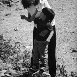 "Black and white photo: Mother and young son outside, son is standing on small boulder with mom behind steadying him with a hand. Son is looking up at mom and signing ""bug""."