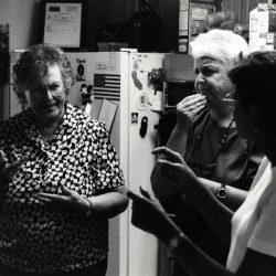 Black and white photo: Three women standing in a kitchen with a white refrigerator behind them. They are deep in discussion, one woman with short grey hair signing, one woman with short white hair, a look of serious consideration and her hand on her chin.