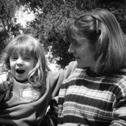 Black and white photo: Mom and daughter are sitting out side with green trees behind them. Their bodies are facing the camera, daughter looking directly at it and pointing, mom looking at her daughter with a gentle smile.
