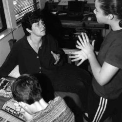 "Black and white photo: Mom, son and daughter are in a home office. Son is looking at a book with his back to the camera. Daughter is signing ""paper"" to mom. Mom is looking up at daughter with a concerned look on her face."