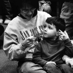 Black and white photo: Close up of mom sitting on the floor with her young son sitting her lap. They are looking at each other and signing. Mom is wearing a San Jose State sweater and son is wearing a dark turtleneck shirt and jeans.
