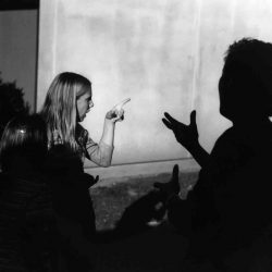 "Black and white photo: Three women standing outside in front of a concrete wall. Two have their backs to the camera, lighting makes them only visible in silhouette. The third woman is lighted to be visible, looking to the side. She is pointing, indicating ""look"" while one other woman is signing ""what"" and the third is signing ""ah, i see""."