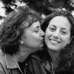 Black and white photo: daughter is looking into the camera smiling while her mom is kissing her on the cheek. They are sitting outside in front of a tree, wearing denim tops. They have similar brown curly hair.