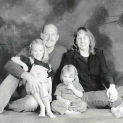 Black and white photo: Peterson family portrait, all are sitting barefoot on the floor in front of a mottled portrait backdrop. Michael and Laura are wearing jeans, their two young blond daughters are wearing overalls.
