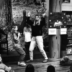 "Black and white photo of mother and daughter on a children's reading stage. Mom has her hands raised and mouth wide open, daughter is holding a doll and expressing surprise. Children are sitting around them in a semi circle watching with attention. There is a backdrop behind them with a drawing of a tree, rabbit and duck. A handprinted sign next to them says ""featuring our storytellers"" with an open book below."