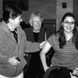 Black and white photo of three white women from three generations, 20's something daughter with long straight brown hair and glasses, wearing a striped shirt, mother with short brown hair and glasses, wearing a zip up hoodie and grandmother with short curly grey hair, wearing glasses and a dark coat. Mother and grandmother are welcoming home the daughter who is pushing a bag. They are all smiling.