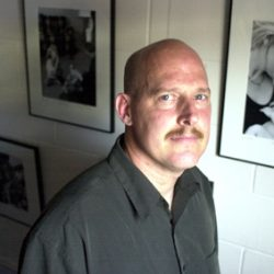 Michael is a white man, bald with a mustache and dark grey button up shirt. He is looking at the camera, behind him are several of his black and white Deaf Mother photos.